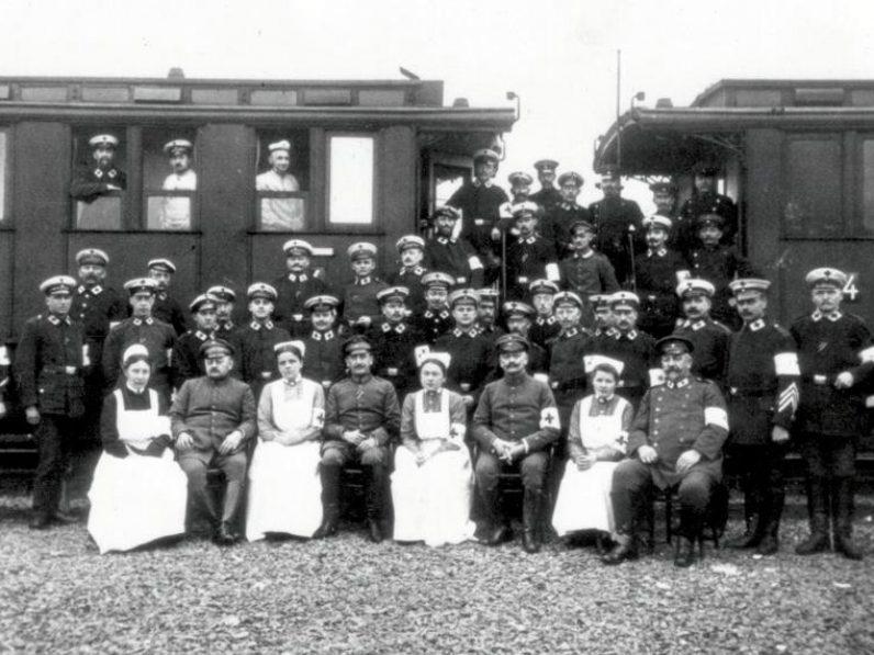 Histroische Aufnahme mehrerer Militärangehöriger und Krankenschwestern, die vor einem Zug posieren.
