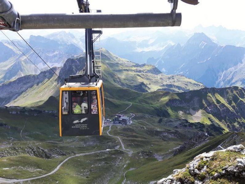 Mehrere Personen stehen in einer Seilbahn und fahren einen Berg hoch.