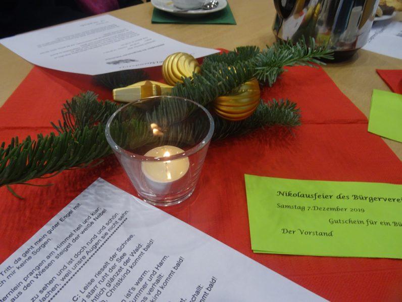 Nahaufnahme der Tischdeko der Nikolausfeier. Man sieht ein Teelicht in einem Glas auf einer roten Serviette, daneben liegt ein Tannenzweig mit goldenen Kugeln.