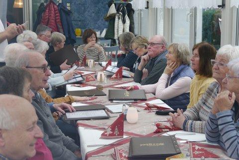 Die Wandertruppe sitzt in einem Restaurant an einem langen Tisch und unterhält sich.