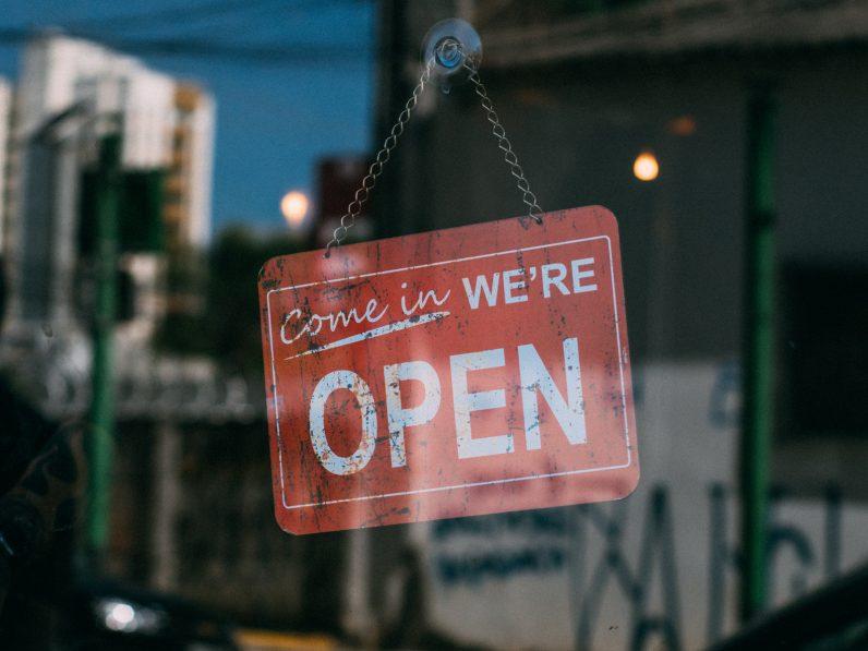 """Schild in einer Ladentür auf der in Englisch steht: """"Geöffnet"""""""