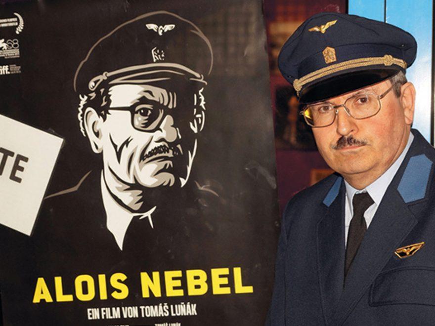 """Michael Kühle steht neben einem Filmplakat zu """"Alois Nebel"""" in Bahneruniform"""