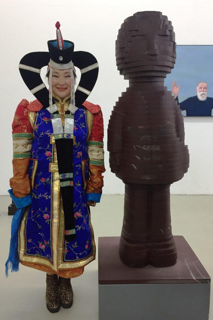 Die mongolesische Sängerin Badamkhorol Samdandamba steht neben einer Engels-Skulpur