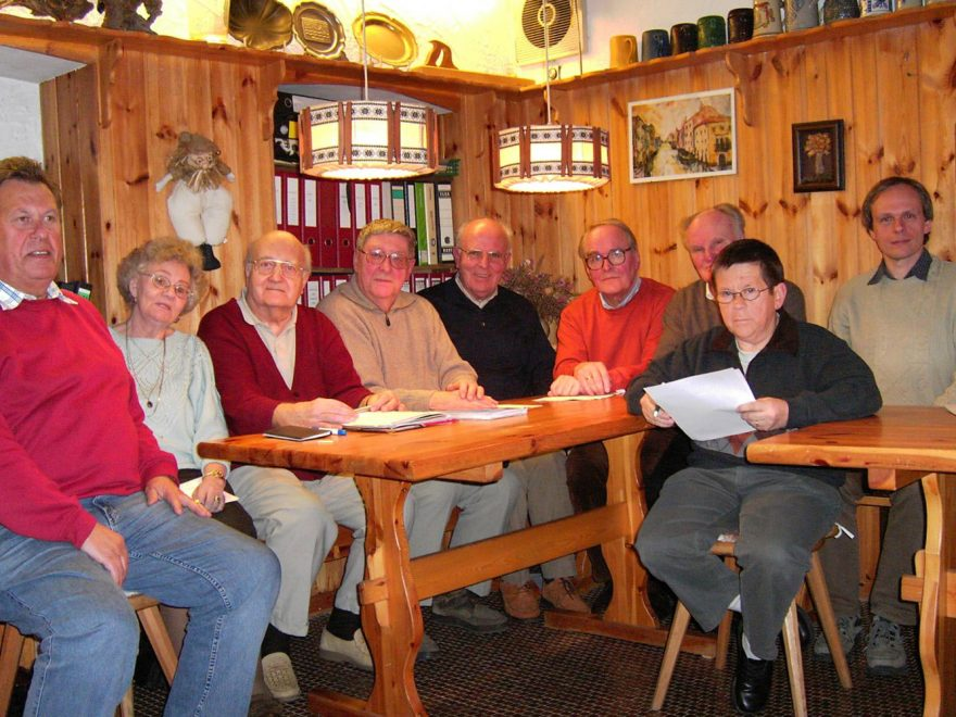 Mitglieder des Bürgervereins sitzen gemeinsam an mehreren Holztischen.