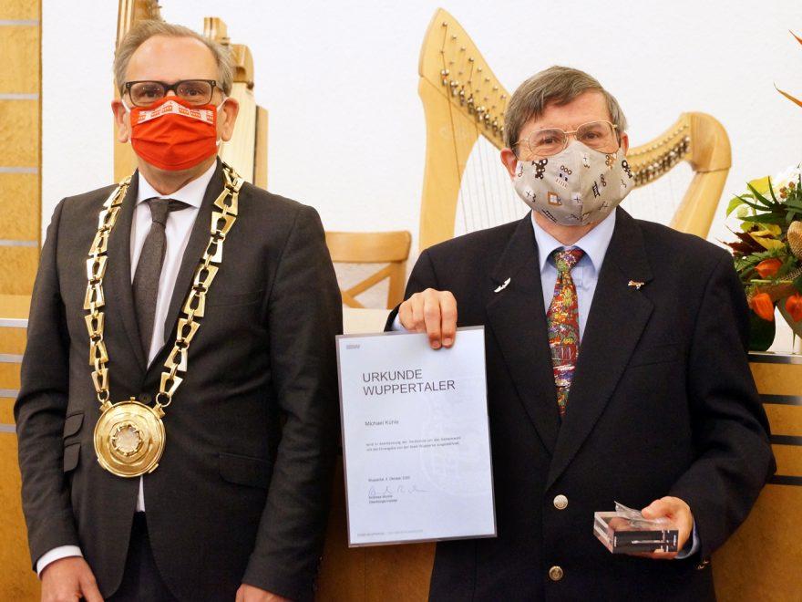 Michael Kühle posiert mit seiner Auszeichnung. Neben ihm steht der Bürgermeister.