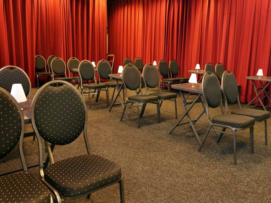 Innenraum des BürgerBahnhof mit einzelnen Tischen und Stühlen.