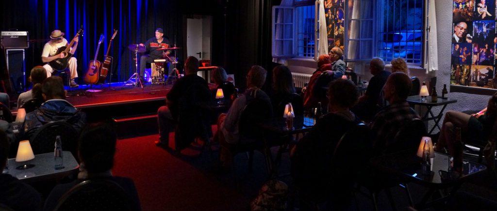 Ein Konzert im BürgerBahnhof. Musiker sitzen auf der Bühne und spielen, das Publikum sitzt davor an Tischen.